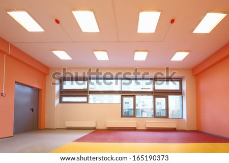 Empty gym with orange walls and large windows in the kindergarten