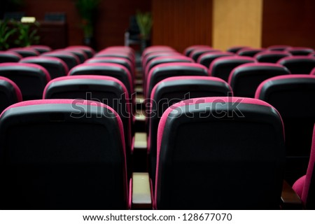 Empty hall for presentation with red armchairs.