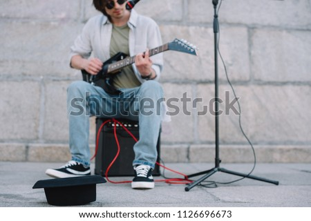 Empty hat in front of busker playing guitar and singing in urban environment