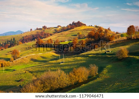 empty hay barracks on a grassy hill among trees in red foliage. beautiful autumn scenery in the distant valley. rural lifestyle #1179046471