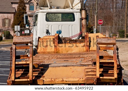 Empty heavy equipment trailer being pulled down a residential street