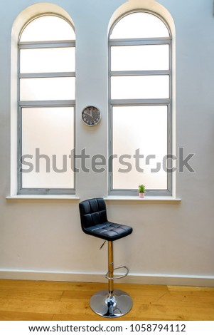 Empty high chair next to cactus in flower pot in a bright window and clock on wall