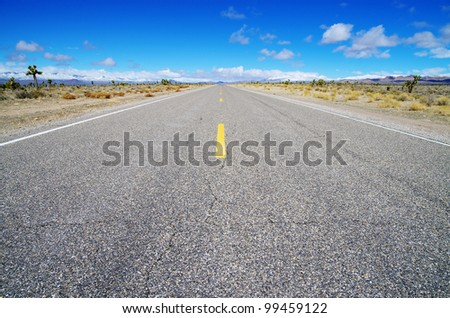 empty high desert road heading straight across Nevada