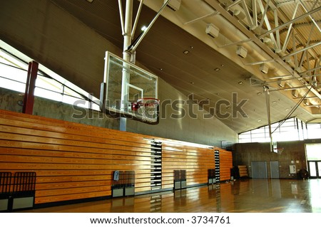 Empty high school gym with basketball hoop and bleachers