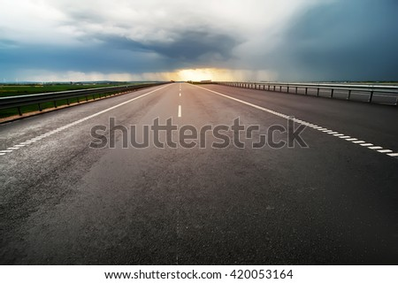 empty  highway asphalt road and beautiful dramatic cloudy sky