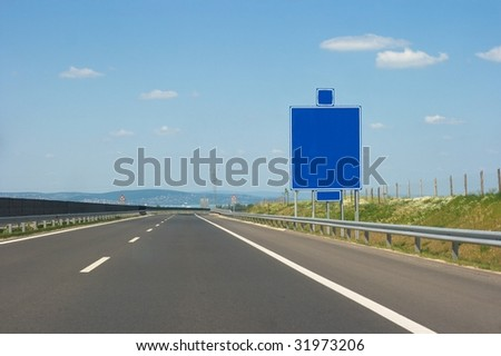 Empty highway lanes and blank signboard