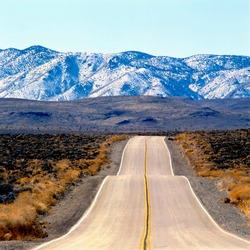 Empty Highway running in the US desert near Death Valley National Park, California, with no cars