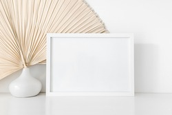 Empty horizontal white wooden picture frame mockup with a small modern white vase and dried palm leaf in front of a white wall