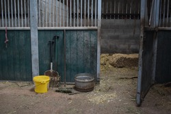 Empty horse stable stall. To be prepared for horses with straw to put as bedding. Fork, brush, shovel, feed bowl and water bucket at the stable entrance.