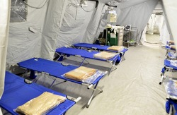 Empty hospital field tent for the first AID, a mobile medical unit of red cross for patient with Corona Virus. Interior camp room with folding camp bed  for people infected with an epidemic. 2019-ncov