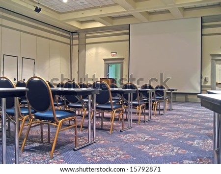 Empty hotel conference room with tables, chairs and projection screen.