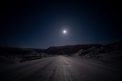 Empty icy road in a remote location in Iceland illuminated by only moonlight and with a starry sky on a clear night.
