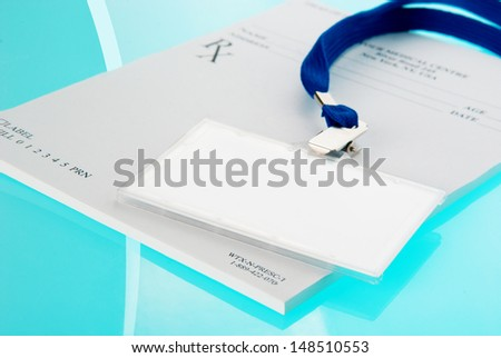Empty ID tag and medical prescription on blue, reflective background