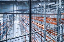 Empty industrial warehouse with racks pallets shelves. Storage equipment. New distribution storehouse. Metal construction.