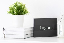 Empty interior black mock up with plant and books, with  Swedish word Lagom meaning