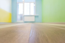 Empty kids room interior background with color walls and wooden flooring, shallow depth of focus