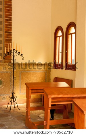 Empty kneelers in a church with light shining through the window on candles
