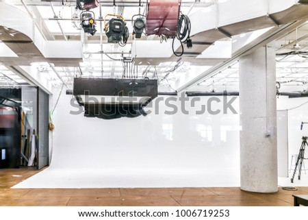 Empty large commercial photography video studio with equipment, lights and white backdrop