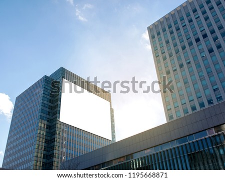 Empty large white screen display for your mock up, advert, product , text on high-rise buildings in the business area in bright day time.
