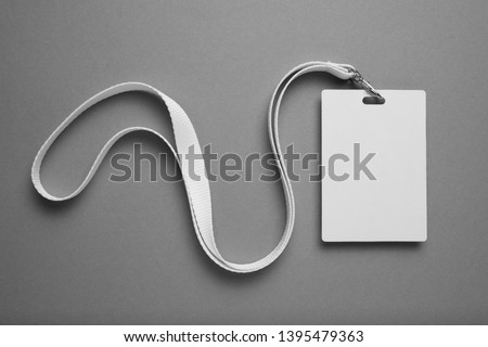 Empty layout layout on grey background. Common blank label name tag hanging on neck with thread.