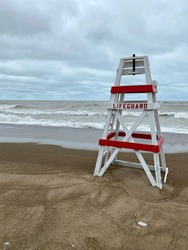 Empty lifeguard chair sits on a Lake Michigan beach on a stormy day as waves crash along the shore in the background. The beach is closed due to rough water and gale wind warnings.