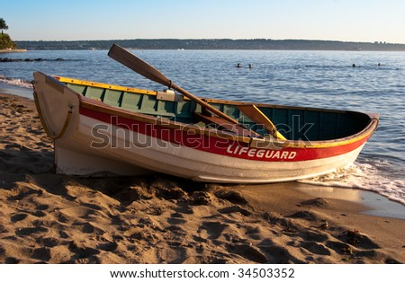 Empty lifeguard rowboat on beach at sunset - stock photo