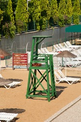 Empty lifeguard tower and beach. Sun loungers among the yellow sands