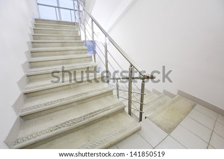 Empty light and simple staircase with metal railings and white walls.