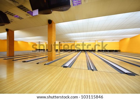 Empty light bowling club, lot of bowling lanes, yellow walls