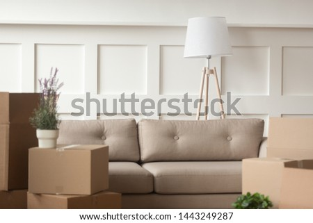 Empty light living room with cardboard boxes with personal belongings, cozy beige couch in apartment interior design, unpacked carton packages, family packing moving relocating to new flat