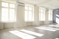 Empty light white room with window with sunlight. Minimalist interior design with natural daylight in a modern building. Sun rays on the floor in the hall.