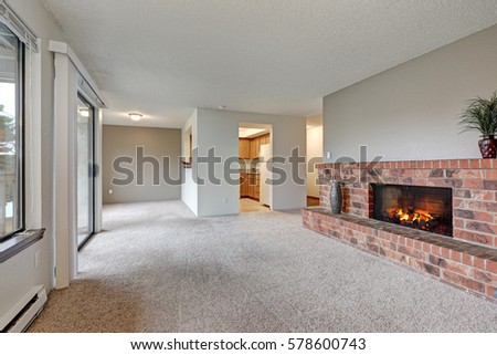 Empty living room features white walls, carpet floor and red brick fireplace. Northwest, USA