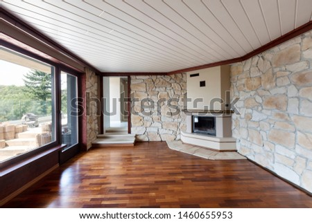 Empty living room with parquet, fireplace, windows and rock on the walls. Nobody inside
