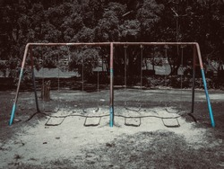 Empty lonely old chain swing set on playground in public park. Childhood memories concept