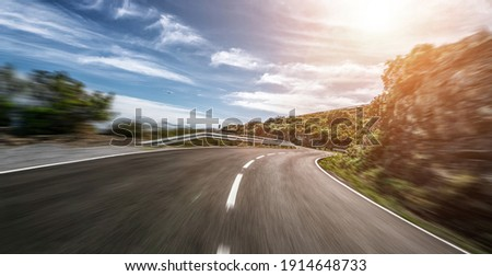Empty long mountain road to the horizon on a sunny summer day at bright sunset - speed motion blur effect