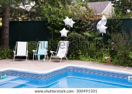 Empty loungers at the backyard pool waiting for party guests to arrive