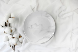 Empty marble plate with cotton flowers on white silk background. Elegant minimalist wedding table setting. Top view.
