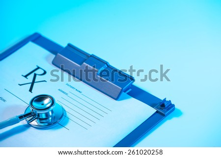 Empty medical prescription and Stethoscope on blue, reflective background
