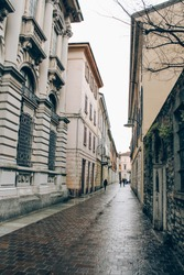 Empty medieval ancient streets in Como city, Lombardy, Italy. Vertical image of cityview with historical buildins and villas around in gloomy winter day, selective focus