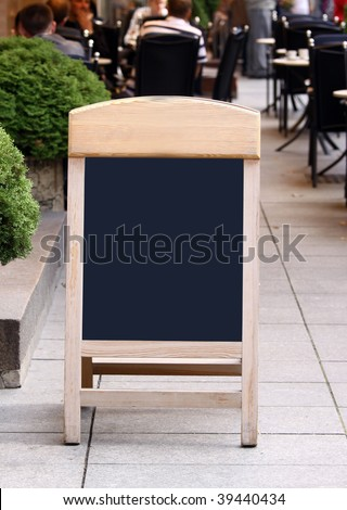 Empty menu board standing on the street and people seen eating on the blurred background