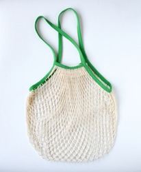 Empty mesh shopping bag, white net cotton string with green holding border on white background. Tote Bag contain vegetable or fruit, reuseable and washable, Eco market bag concept.