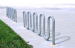 empty metal bike rack in parking lot of campus