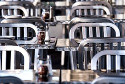 empty metal tables and chairs with salt and pepper shakers at an outdoor restaurant