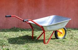 Empty metal wheelbarrow in a spring garden. Garden trolley close up.