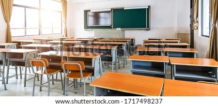 Empty modern classroom with chairs, desks and chalkboard.
