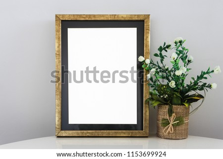 Empty Modern Golden Frame On White Glossy Table With Decorative Flowers.Light Gray Background Wall (White Blank Advertisement Banner Mock Up Isolated Template)