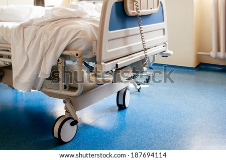 Empty modern hospital bed in a sunny room with a clean blue floor