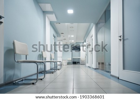 Empty modern hospital corridor, clinic hallway interior background with white chairs for patients waiting for doctor visit. Contemporary waiting room in medical office. Healthcare services concept
