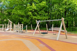 Empty modern outdoor playground in summer. A beautiful place for children's games, sports and recreation with benches, swings and slides. Safe rubber floor covering for baby's health