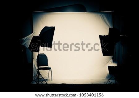 Empty modern photo studio with professional lighting equipment. Halogen lighting, Spotlight and umbrella backstage setup behind the shooting production and silhouette of equipment in photo studio.